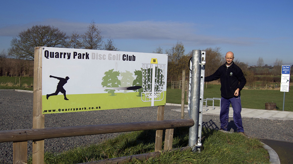 Derek Robins opening the gate to his private disc golf course near Birmingham, England